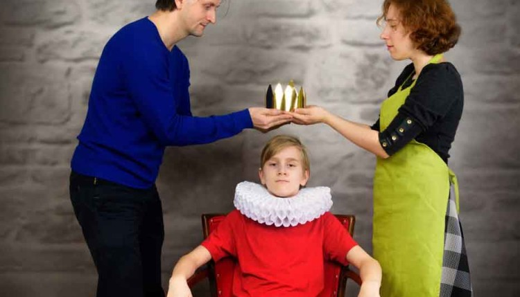 Parents put a crown on the head of their son. Permissive (indulg